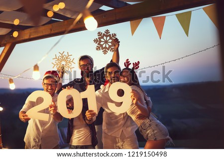 Group of young friends having fun at a New Year's Eve outdoor pool party, dancing and holding cardboard snowflakes and numbers 2019. Focus on the couple on the right