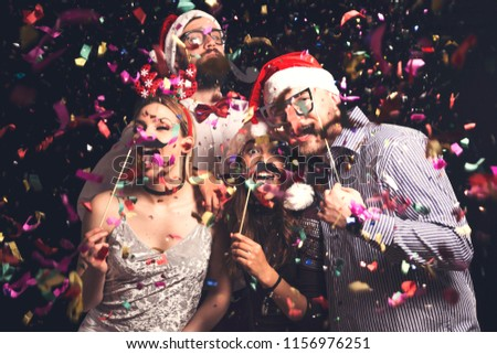Group of young friends having fun at New Year's Eve Party, posing for photos with masks #1156976251