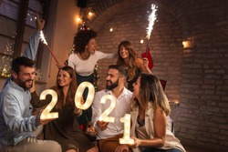 Group of young friends having fun at New Year's party, holding illuminative numbers 2021 representing the upcoming New Year and waving with sparklers at midnight countdown