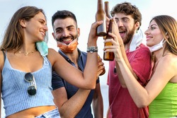 Group of young friends having fun drinking and clinking with beers after the coronavirus lockdown. Happy people with protective masks toasting with beer bottles together.
