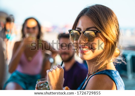 Group of young friends having fun drinking cocktails on the beach. People making alcoholic aperitif in the summer. Focus on a girl with mirrored sunglasses.