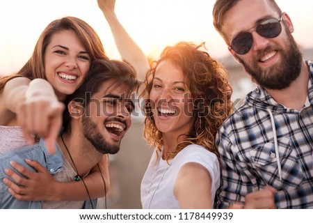 Group of young friends having fun on a summertime rooftop party. Focus on the girls #1178449939