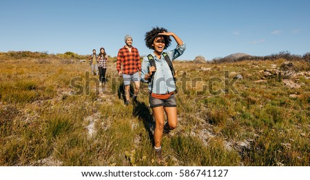 Group of young friends hiking in countryside. Multiracial young people on country walk.