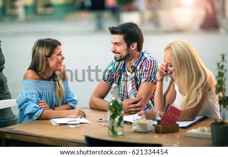 Group of young friends laughing in cafe enjoying on sunny spring day #621334454