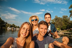 Group Of Young Friends On A Boat Enjoying Sunny Day And Taking Selfie