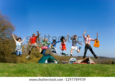 Group of young friends on camping vacation jumping in mid air smiling at camera