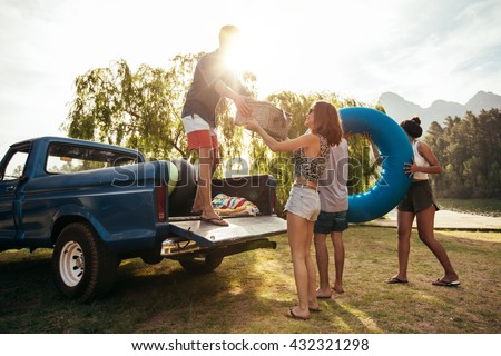 Group of young friends on picnic by the lake. Men and women unloading pickup truck on camping trip, carrying picnic basket and inflatable tube on sunny day.
