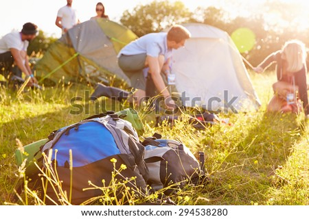 Group Of Young Friends Pitching Tents On Camping Holiday