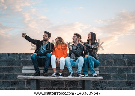 Group of young friends singing and taking selfie outdoors with a smartphones. Young people having fun using new technologies sitting on an outdoor bench.