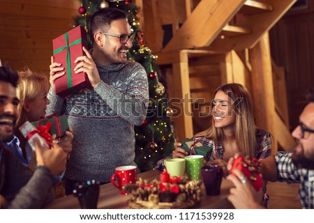 Group of young friends sitting next to a nicely decorated Christmas tree, exchanging Christmas presents and having fun