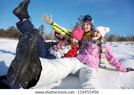 group of young friends tumbles in the snow on a winter vacation