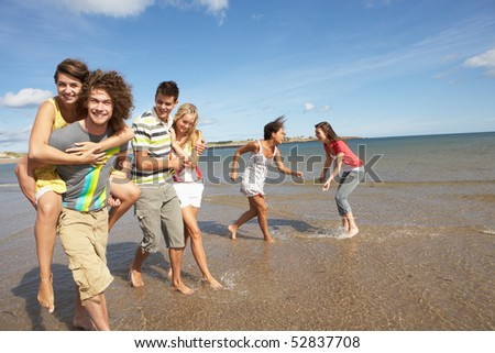Group Of Young Friends Walking Along Summer Shoreline