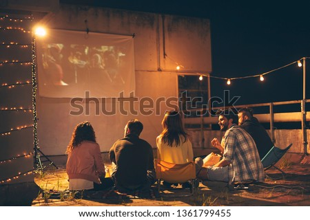Group of young friends watching a movie on a building rooftop terrace, eating popcorn, drinking beer and having fun