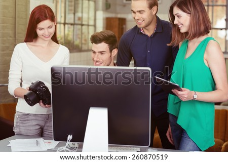 Group of Young Friends Watching Photos on a DSLR Camera Together Behind a Computer Screen.