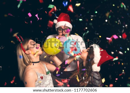Group of young friends wearing Santa hats at New Year's Eve party at midnight blowing colorful balloons and having fun #1177702606