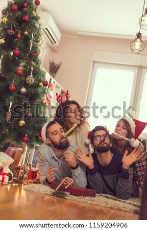 Group of young frineds lying on the floor next to a Christmas tree, having fun blowing party whistles. Focus on the girl on the left