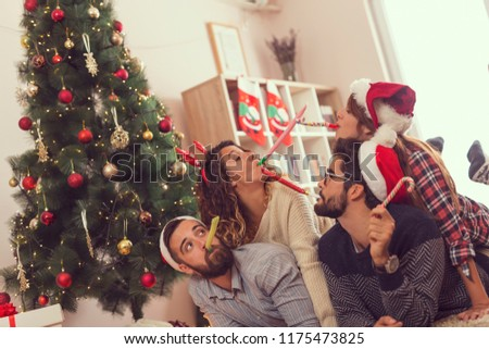 Group of young frineds lying on the floor next to a Christmas tree, having fun blowing party whistles