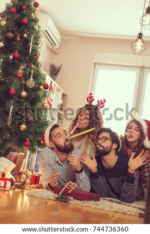 Group of young frineds lying on the floor next to a Christmas tree, having fun blowing party whistles. Focus on the guys
