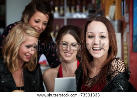 Group of young girlfriends having a good time together in a cafe