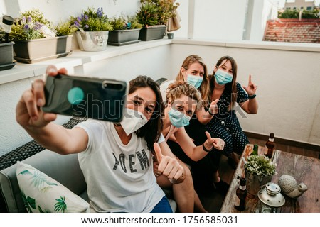Group of young girlfriends meeting after the quarantine caused by the covid19. Taking precaution with surgical masks and taking photos together with a smartphone.
