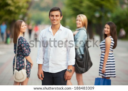Group of young girls flirting with young man in the city.
