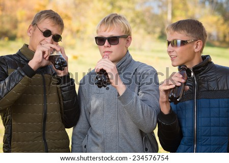 Group of young guys drink beverages and communicate with each other. Two of the boys twin brothers. Image with Instagram-like filter