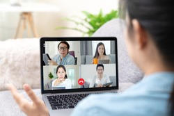 Group of young happy asian work from home meeting or brainstorming online video conference application on 5G internet with covid coronavirus business continuity plan via tablet or notebook computer.
