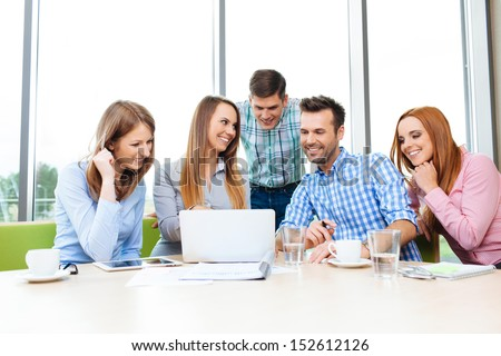 Group of young happy employees working together with laptop