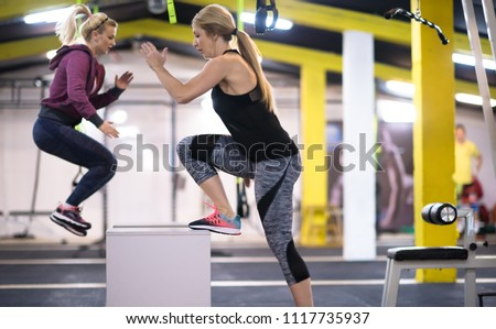 group of young healthy athletic people training jumping on fit box at cross fitness gym #1117735937