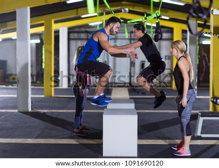 group of young healthy athletic people training jumping on fit box at gym #1091690120