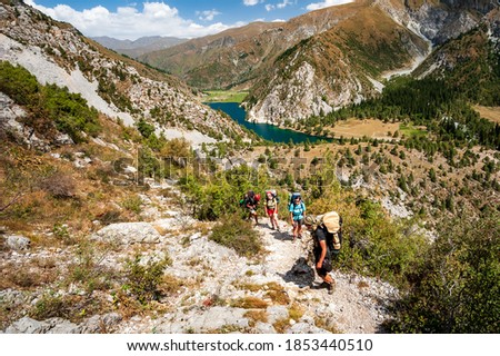 Group of young hikers trekking in mountains. Two women two men backpacking in summer near Sary Chelek lake, Sary-Chelek Jalal Abad region, Kyrgyzstan, Trekking in Central Asia. Zdjęcia stock ©