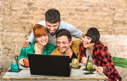 Group of young hipster best friends with computer in urban alternative studio - Friendship fun concept with millennials new trend technology - Start up entrepeneurs at work together drinking cocktails