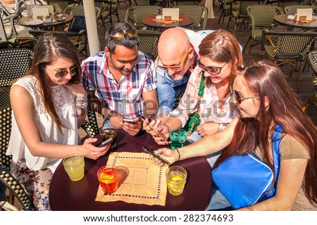 Group of young hipster friends having fun together with smartphone at restaurant bar - Technology concept of interaction in everyday lifestyle - Internet connection spot outdoor - Sunny day color tone