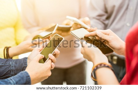 Group of young hipsters holding phone in hands. Friends having fun together with smartphones.