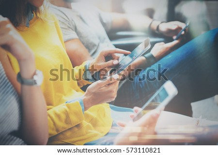 Group of young hipsters sitting on sofa holding en hands and using digital tablet,smartphone.Coworking team concept.Horizontal,blurred background #573110821