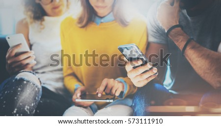Group of young hipsters sitting on sofa holding en hands and using electronic gadgets.Coworking teamwork concept.Horizontal,blurred background
