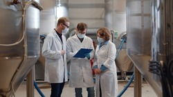Group of young inspectors in white coat and safety mask conducting audit at beer factory. Portrait of technologists wearing protective mask, gloves and lab coat inspecting brewery plant