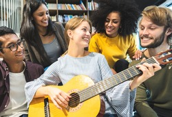 Group of young international tourists meeting in bed and breakfast party living room while playing guitar and singing- Concept of Friendship