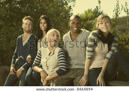 group of young interracial friends having fun in a park