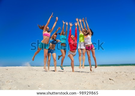 Group of young joyful girls playing on the beach