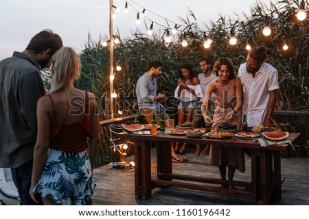 Group of young men and women enjoying summer holiday at outdoor party. ストックフォト ©