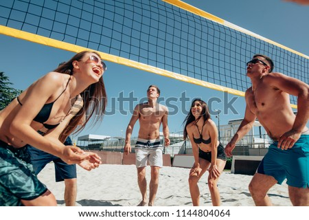Group of young men and women playing beach volleyball on sand. Summer vacation, sport, games and friendship concept - playing valleyball outdoors