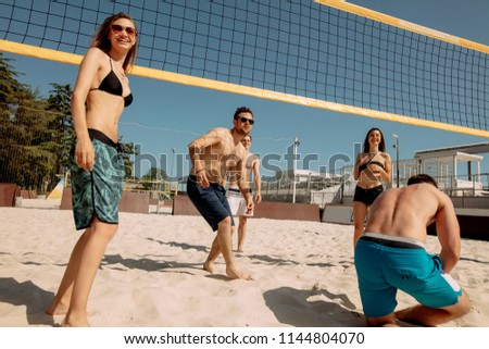 Group of young men and women playing beach volleyball on sand. Summer vacation, sport, games and friendship concept - group of happy teenagers playing valleyball outdoors