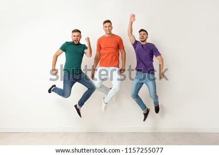 Group of young men in jeans and colorful t-shirts jumping near light wall #1157255077