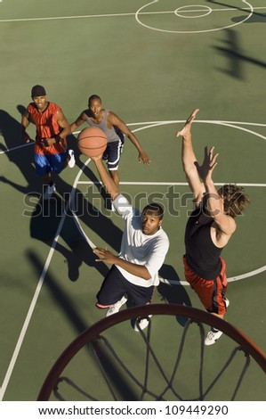 Group of young men playing basketball in court