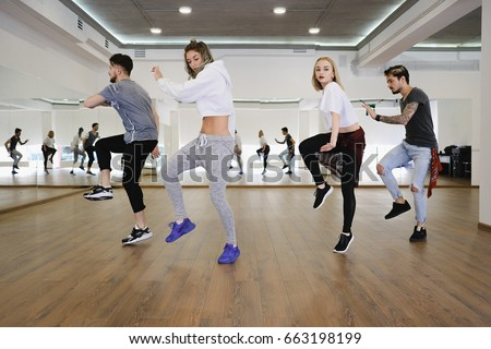 Group of young modern dancers dancing in the studio. Sport, dancing and urban culture concept #663198199