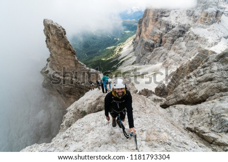 group of young mountain climbers on a steep Via Ferrata with a grandiose view of the Italian Dolomites in Alta Badia behind them