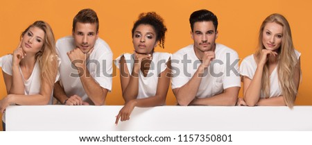 Group of young multi-ethnic beautiful people wearing white shirts, posing together with empty white board. Cheerfull smiling friends. #1157350801