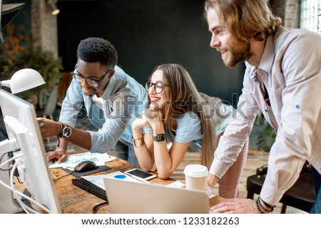 Group of young multi ethnicity coworkers dressed casually working together focused on the computer monitor indoors