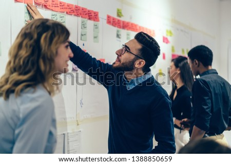 Group of young multicultural perspective managers creating idea of strategy for productive work of company, curiosity male expert in optical spectacles reading interesting note from sticks on wall #1388850659